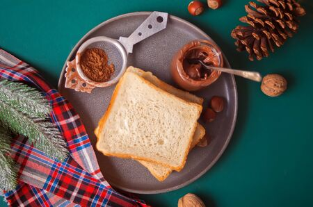 Bread toast with chocolate cream, jar of milk on the green background with Christmas decoration. Top view.