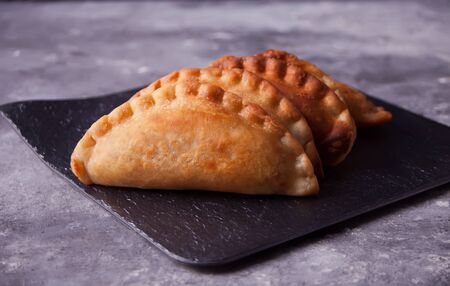 Mexican fried meat pies empanadas cheburek on the black plate on the concrete background.