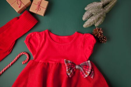 Red dress with checkered bow, tights, candy cane, gift box and pine branch on the green background. Christmas party fashion for girls. Top view. Imagens