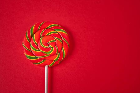Rainbow color lollipop hard caramel on the stick on red background. Copy space. Top view Imagens