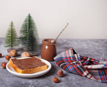 Bread toast with chocolate cream butter, miniature Christmas trees toys on the concrete background.
