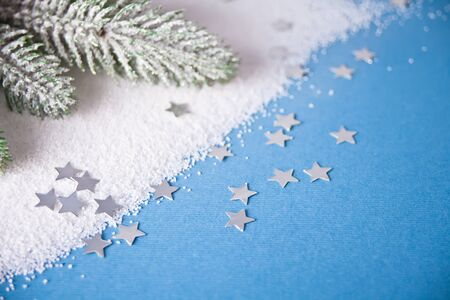 Christmas tree branch on the blue background with small snowflakes.