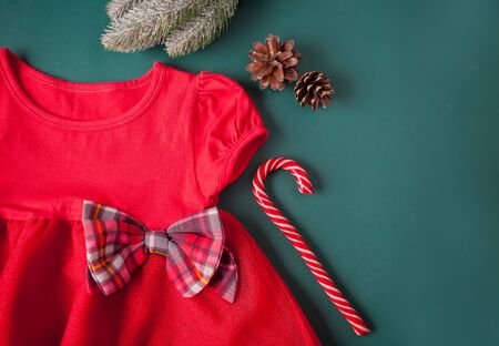 Red dress with checkered bow, tights, candy cane on the green background. Christmas party fashion for girls. Top view. Copy space.