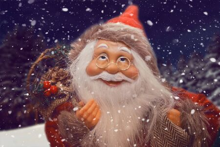 Christmas is coming. Santa with gifts smiling. Winter landscape on the background.