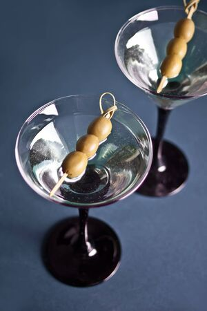 Two glasses of martini with olives on the blue background