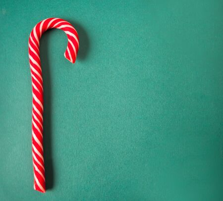 Candy cane hard caramel on green background. Copy space. Top view Imagens