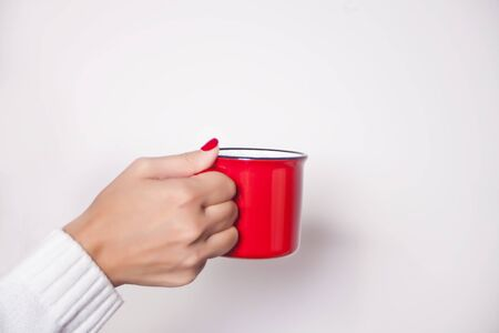 Womans hand holding red mug on the white background.