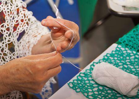 Senior woman knitting lace shawl at home. Imagens