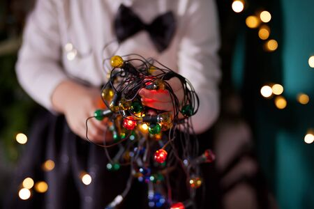 The girl is holding a Christmas garland in her hands. Warm Christmas mood.