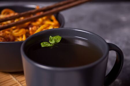 Udon noodles with chicken meat in bowl with chopsticks and cup of tea on dark stone background. Banco de Imagens
