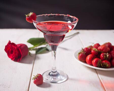 Roter exotischer alkoholischer Cocktail in Klarglas, Teller mit frischen Erdbeeren und roter Rose auf dem weißen Holztisch für romantisches Abendessen