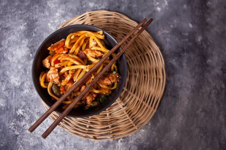 Udon noodles with chicken meat in bowl on dark stone background. Top view