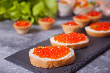 Fresh red caviar on bread on the black plate. Sandwiches with red caviar