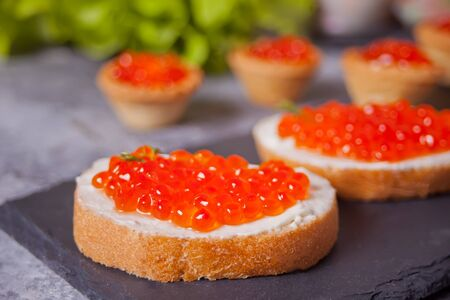 Fresh red caviar on bread sandwiches on the black plate. Tartlets with red caviar on the background. Stock fotó