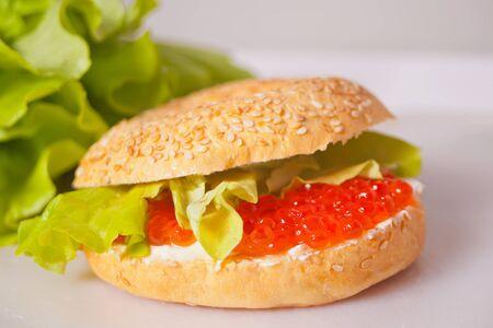 Fresh red caviar on bread bagel. Sandwiche with red caviar. Delicatessen. Gourmet food.