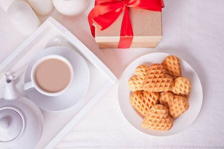 Cup of milk tea, heart shaped cookies and gift box on the white table