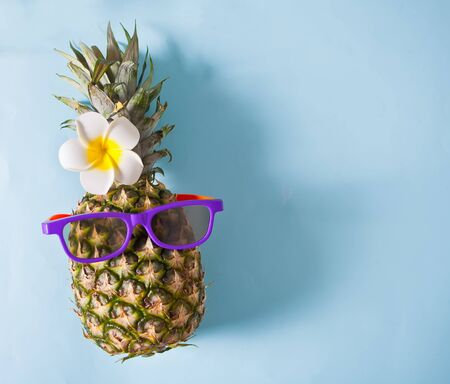 Juicy pineapple in sun glasses on blue background. Copy space. Top view.