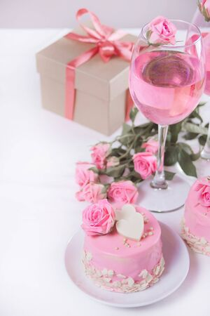 Mini cake with pink glaze, beautiful roses, cup of coffee, gift box on the white table. Copy space.