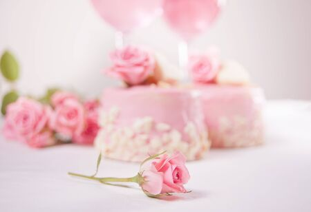 Two mini cakes, glasses with pink grape wine and rose flowers on a white table. Romantic dinner concept.