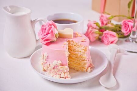 Mini cake with pink glaze, beautiful roses, cup of coffee, gift box on the white table Banque d'images - 140642782