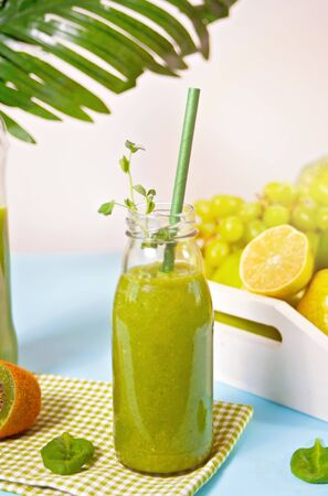 Fresh blended green smoothie in glass small bottle with fruit and vegetables on the background. Health and detox concept Banco de Imagens