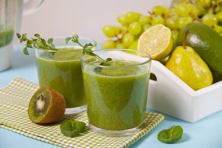 Fresh blended green smoothie in glasses with fruit and vegetables on the background. Health and detox concept