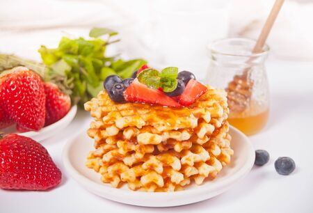 Plate with sweet tasty waffles with honey, berries, cup of tea on the white background