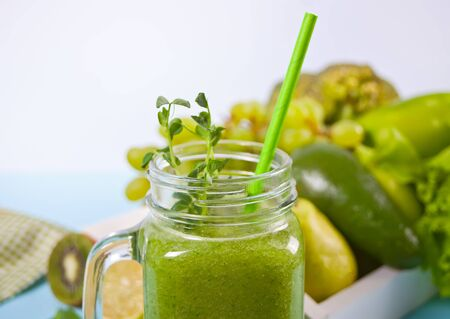 Fresh blended green smoothie in glass jar with fruit and vegetables on the background. Health and detox concept