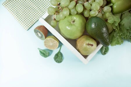 Composition with assorted raw organic green vegetables and friuts on the white wooden tray. Top view. Copy space