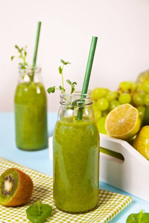 Fresh blended green smoothie in glass small bottles with fruit and vegetables on the background. Health and detox concept Banco de Imagens