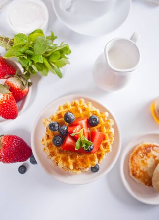 Plate with sweet tasty waffles with honey, berries, cup of tea on the white background. Top view.