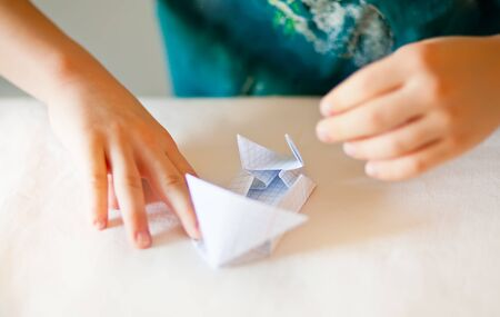 Children kid hands do origami on the white table 版權商用圖片