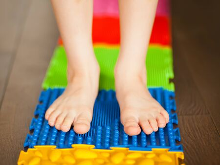 Little boy kid walking on a orthopedic massage mat. Treatment and prevention of flat feet in children