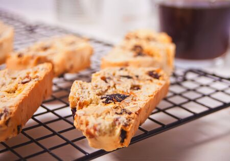 Italian biscotti on the baking rack and glass of coffee on the background.