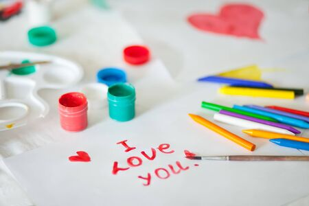 Text I love you drawing with colored paints on the paper. Brushes, paints, gouache on the background