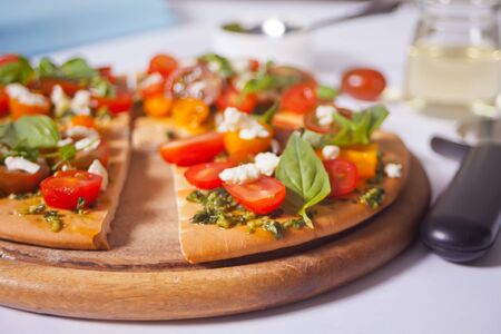 Homemade pizza with cherry tomatoes, fresh green basil and feta cheese. Homemade food. Concept for a tasty and hearty meal. Wooden background. Close up
