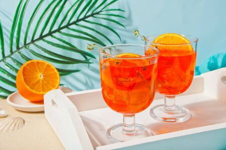 Glasses with fresh homemade orange sweet iced tea or cocktail, lemonade with thyme. Refreshing cold drink. Summer party or picnic.