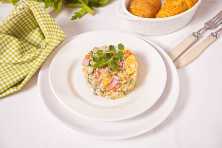 Russian traditional salad Olivier with vegetables and meat in the white plate Zdjęcie Seryjne