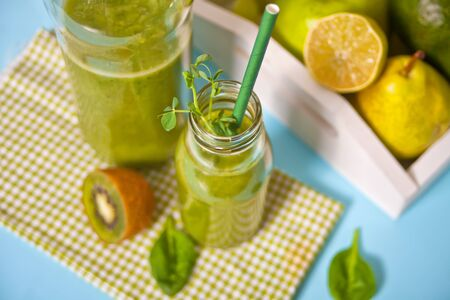 Fresh blended green smoothie in glasses bottles with fruit and vegetables on the background. Health and detox concept