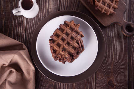 Homemade chocolate waffles on the wooden table.