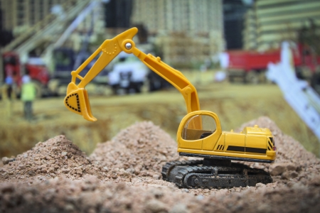 excavator toy at construction site photo