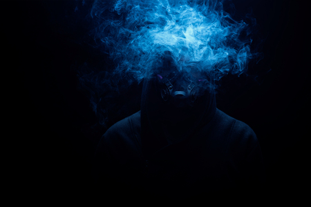Man smoking an electronic cigarette on the dark background with gas mask on face