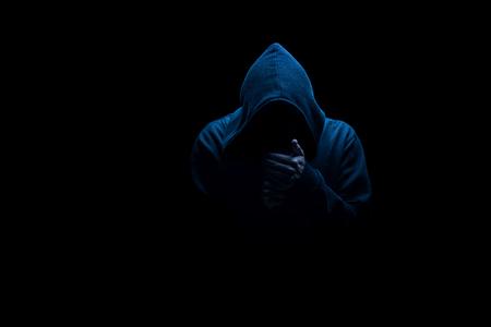 Mann in schwarzer Kapuze in der Nachtdunkelheit, schwach beleuchtet, Konzepte von Gefahrenkriminalität Terror Standard-Bild