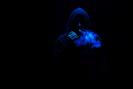 Man smoking an cigarette on the dark background with gas mask on face