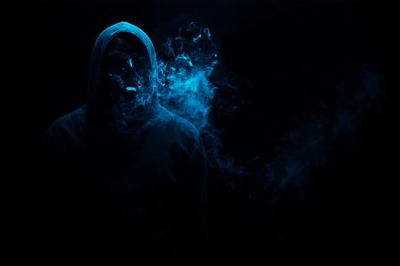 Man in black hood in the night darkness, dimly lit, concepts of danger, crime terror 版權商用圖片