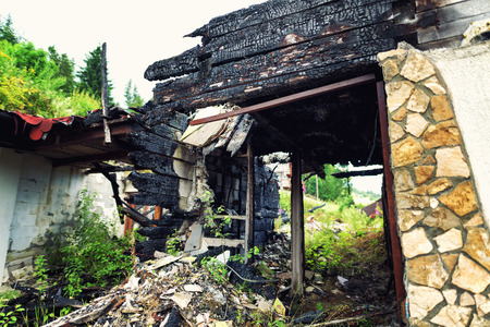 Burnt out house with charred roof and burnt furniture