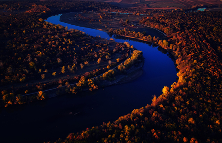 Drone view of stunning warm colorful autumn fall forest at sunset