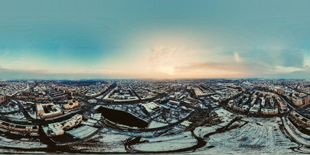 360 panorama of Sun shining over winter city with sun rays hitting the buildings