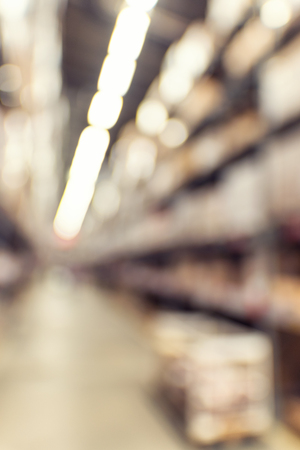 Defocused background of industrial warehouse interior aisle. inventory, hypermarket, wholesale, logistic and export concept