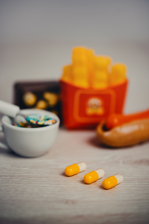 Concept photo of drugs needed to take in order to stay healthy eating junk food 版權商用圖片